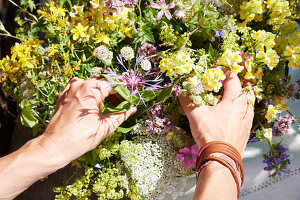 Hände arrangieren Wiesenblumenstrauß