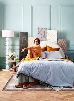 Junge Frau sitzt auf Doppelbett im Schlafzimmer mit mintgrüner Wand