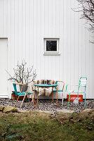Vintage Gartenmöbel mit Fell vor weißem Holzhaus