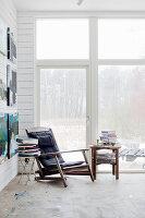 Vintage Sessel und Beistelltische mit Bücherstapel vor Terrassentür, Gemälde an weißer Holzwand