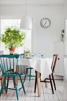Gedeckter Esstisch mit verschiedenen Stühle auf weißem Holzdielenboden