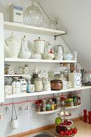 Alte Kannen und Vorratsdosen auf Küchenregalen unter der Schräge