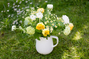 Spring bouquet of tulips, ranunculus and ox-eye daisies in jug