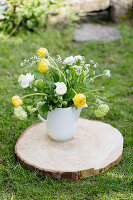Spring bouquet of tulips, ranunculus and ox-eye daisies in jug on slice of tree trunk