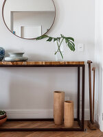 Console table below round mirror on wall