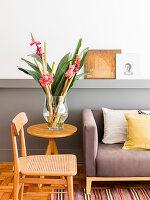 Stuhl und Beistelltisch mit Blumen neben Polstersofa