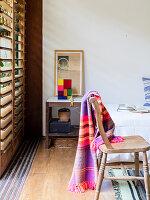 Rustikaler Holzstuhl mit bunter Decke vor Lamellenfenster