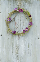 Wreath of heather decorated with purple violas and twig