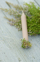 Sprigs of heather wrapped around candle base