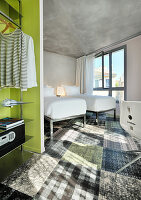 Twin beds in hotel room with concrete ceiling and patchwork carpet
