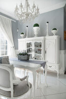 White, antique dresser and dining table below chandelier in elegant dining room