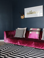 Couch mit pinkfarbenem Samtbezug und Kissen auf schwarz-weiß gestreiftem Teppich vor dunkler Wand