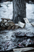 Cast iron pots covered with embers in camp fire in snow