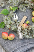 Kuchengabel mit Namensschild zwischen kleinen Äpfeln und Clematis