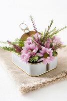 Pink flower arrangement in sardine tin decorating table