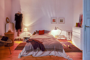 Two lit bedside lamps in bedroom with wooden floor