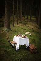 Table in forest set with bundt cake and fruit basket