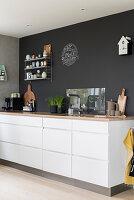 Weiße Küchenzeile mit Schubladen und Holz-Arbeitsplatte vor anthrazitfarbener Wand