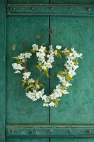 Cherry-blossom heart-shaped wreath on rustic cupboard door