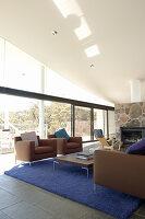 Lounge mit brauner Polstergarnitur, blauem Teppich, Kamin und Glasfront
