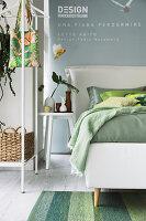 Doppelbett mit Bettkopfteil und Nachttisch neben Garderobenständer