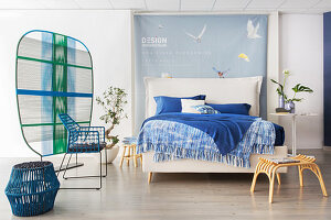 Bettwäsche in Blautönen auf weißem Doppelbett mit Bettkopfteil in offenem Schlafraum mit Raumteiler