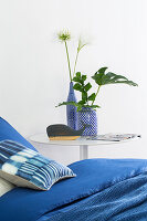 Blue bed linen on bed next to leaves and flowers in blue-and-white vases on bedside table