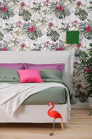 White double bed with headboard against floral wallpaper