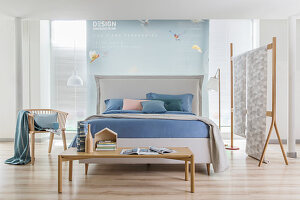 White double bed with headboard and pastel-blue bed linen in open-plan bedroom with partition wall