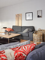 Grey couch, coffee table and baskets in living room