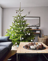 Decorated Christmas tree, Christmas decorations on tray on coffee table and grey couch in living room
