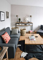 Grey couch, coffee table and festively decorated sideboard in living room