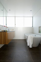Free-standing bathtub and wooden floating washstand in bathroom