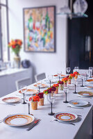 Gedeckte Tafel mit Blumendeko und Weingläsern