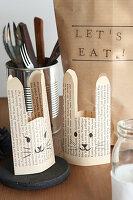 Selbstgemachte Eierbecher aus Buchseiten, bemalt mit Hasengesichtern