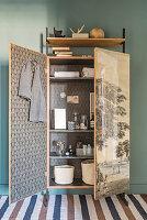 Badeutensilien in restauriertem, altem Kleiderschrank mit Vintage Tapete
