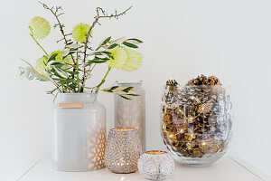 Silk flowers in milk churn, branches of blackthorn and olive, candle lanterns and glass vase filled with pine cones and fairy lights