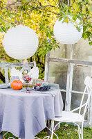Autumnal arrangement on table below paper lanterns in garden