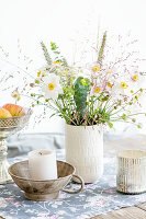 Japanese anemones and grasses in white vase