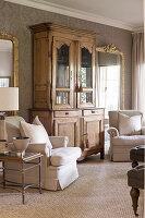 Two cream armchairs flanking antique dresser