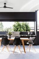 Esstisch mit Klassikerstühlen und Grill auf Wohnterrasse