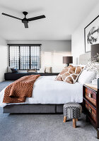 Doppelbett im Schlafzimmer mit grauem Teppichboden, im Hintergrund Sitzbank