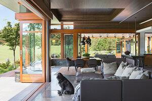 Offener Wohnraum mit grauer Sofagarnitur und Glasfalttür