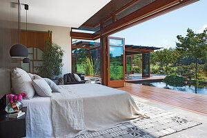 Doppelbett im Schlafzimmer mit offener Terrassentür, Blick auf Pool im Garten