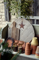 Plant pots, wooden boards, and metal stags arranged on wooden shelf below bunch of mistletoe