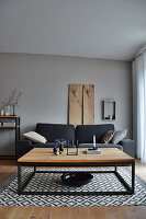 Living room in shades of grey: couch in front of wooden panel and coffee table on rug