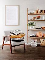 Offenes Bücherregal, Botschaft an der Wand und Sessel mit Kissen