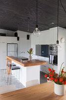 Barhocker an Kücheninsel mit Holzarbeitsplatte, weiße Einbauküche in offenem Wohnraum