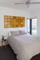 Doppelbett in schlichtem Schlafzimmer mit Vintage Wanddekoration