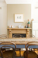 Bistro chairs at wooden table in front of open fireplace in beige wall